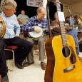 Joe Deetz and George Gruhn checking out banjos behind Carter Stanley's 1941 D-28 Martin guitar at Banjothon 2013 - photo © Dean Hoffmeyer