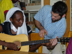 Starr Moss gives guitar pointers to a young student in Maradi